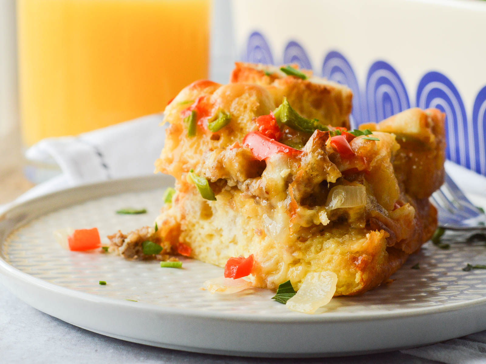 Breakfast Strata with sausage plated with a glass of orange juice in the background. You can see the layers of sausage, peppers, egg and cheese in the baked casserole.