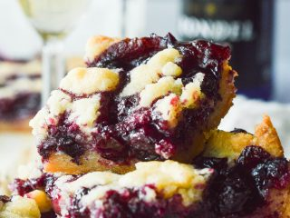 A stack of Blueberry Crumble Bars with several poured glassed of champagne in the background.