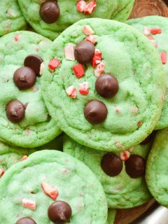 The best Grinch Cookies all piled up on a wooden serving board. they are green and studded with chocolate chips