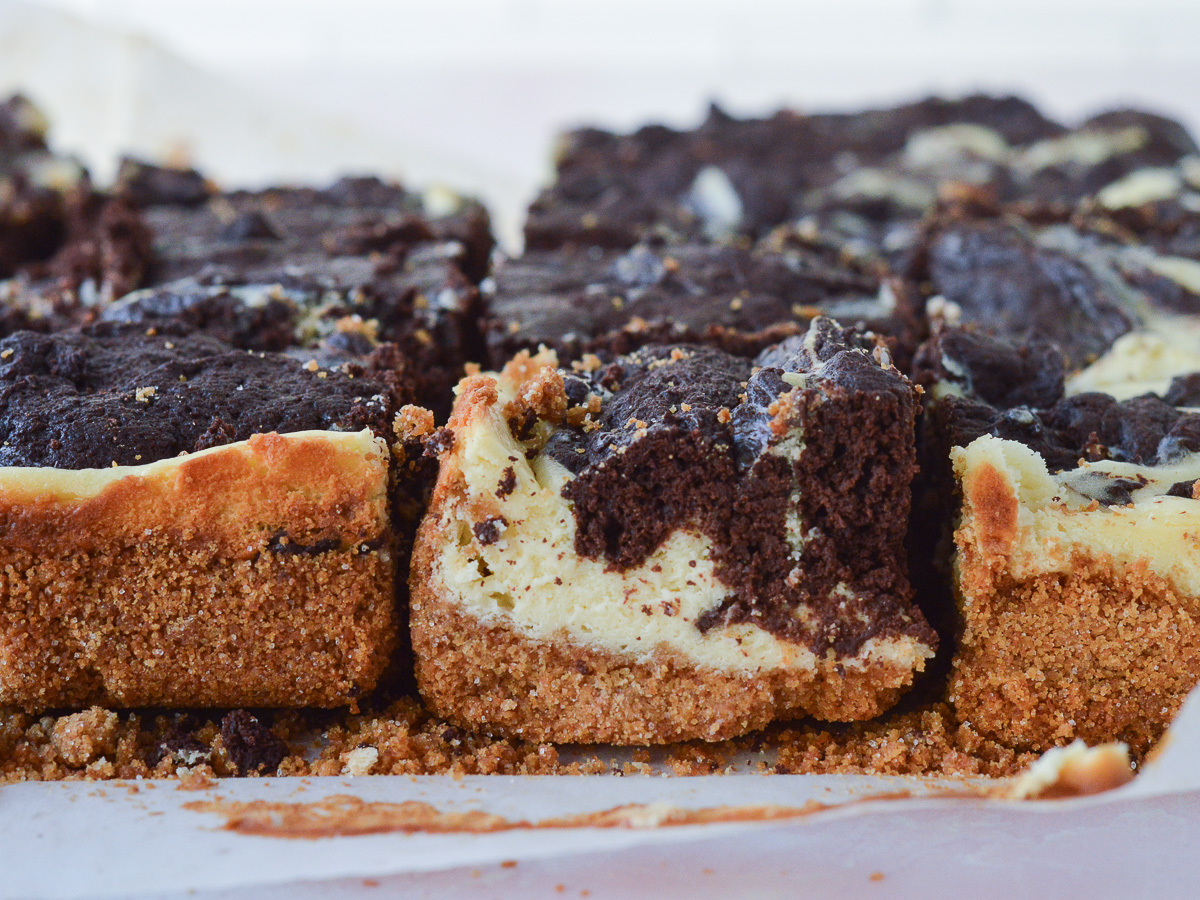A close up of Cheesecake Brownie Bars with Graham Cracker Crust. You can see the buttery graham cracker layer on the bottom, and the swirled brownies + cheesecake in decadent detail.