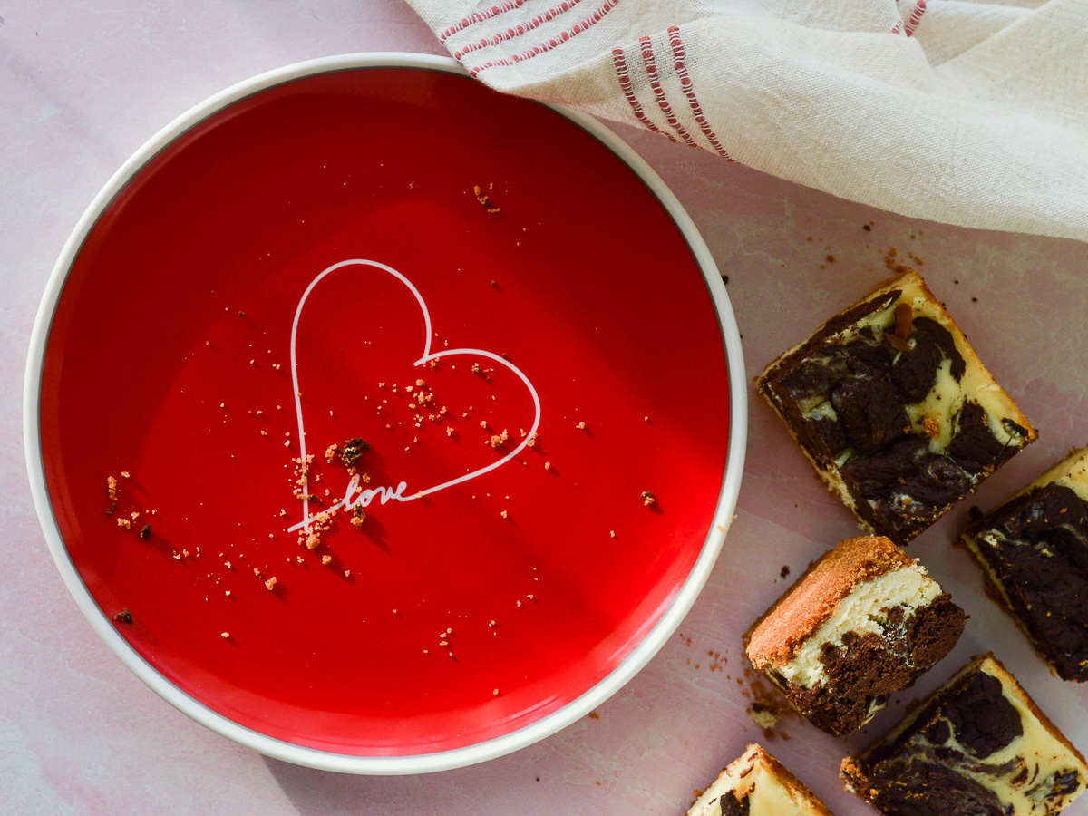 """A red plate with a heart on it and the word """"love"""". There area few graham cracker crust crumbs and a board full of cheesecake brownie bars off to the right side."""