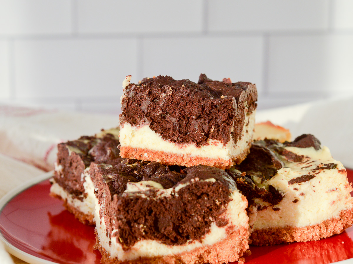 Lancape oriented image of Cheesecake Brownie Bars with a graham cracker crust stacked on a red plate