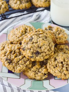 A plate piled high with thick oatmeal raisin cookies, with a glass of milk nearby.
