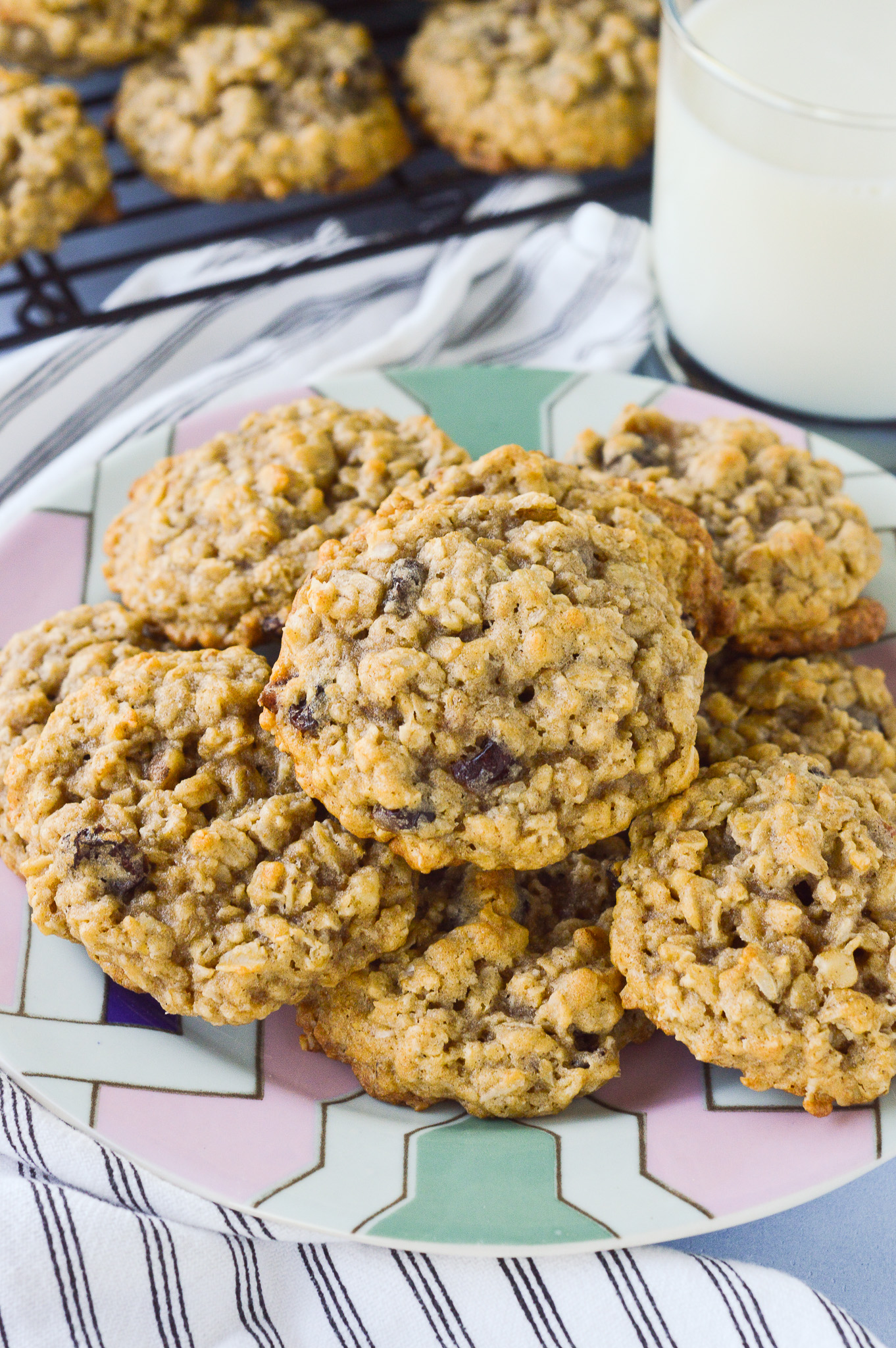 Thick chewy oatmeal raisin cookies piled on a plate with a glass of milk nearby.