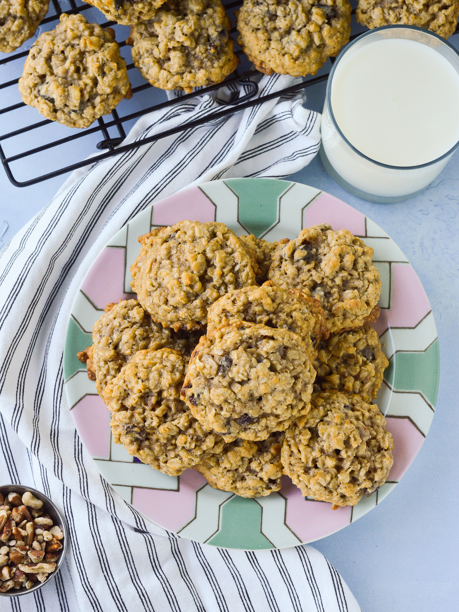 Overhead view of a big plate of Oatmeal Raisin Cookies with a portion of walnuts nearby as well as more cookies cooling on a rack and a glass of milk.