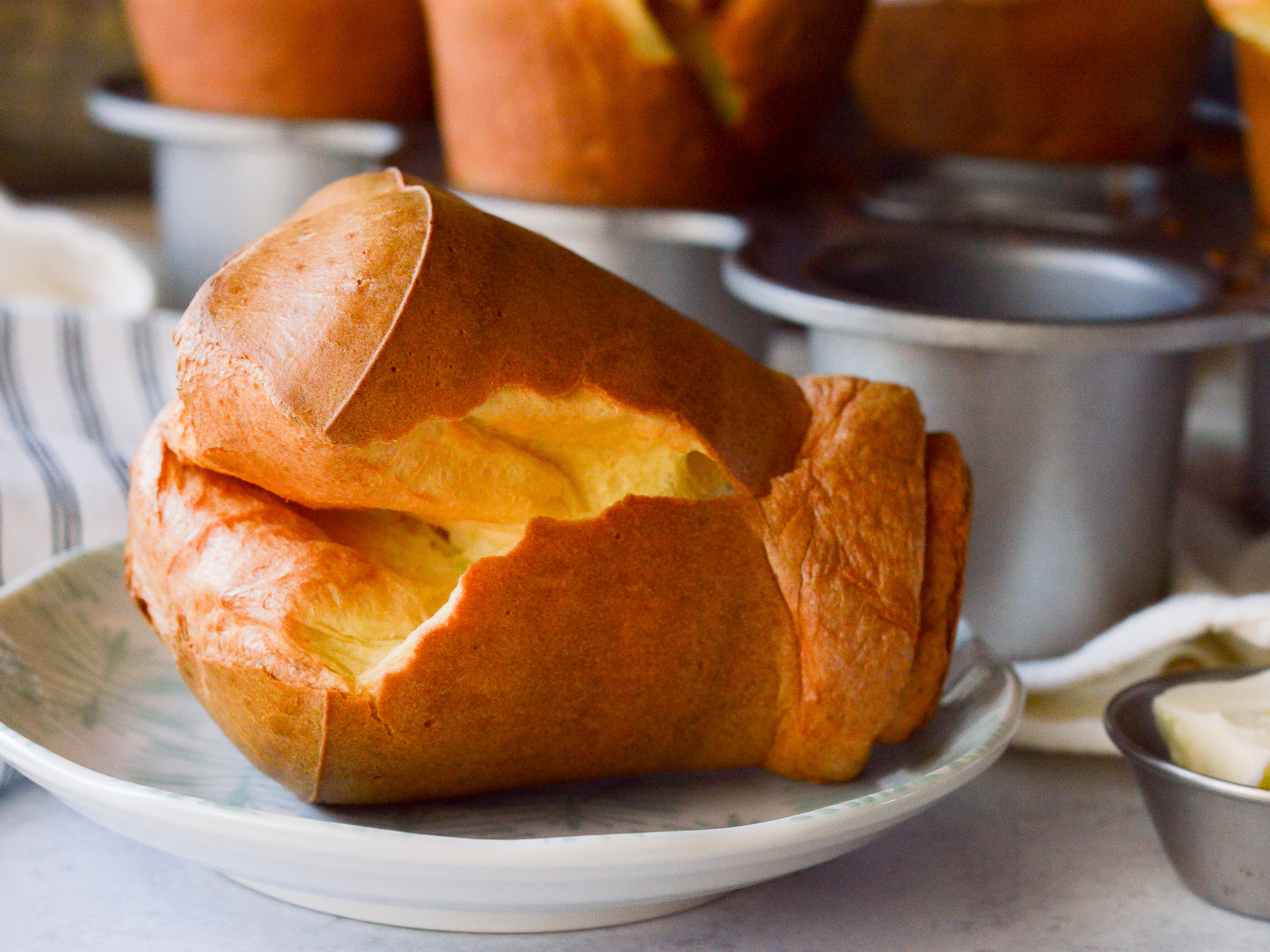 A fluffy popover made using a blender on a small plate ready to eat.
