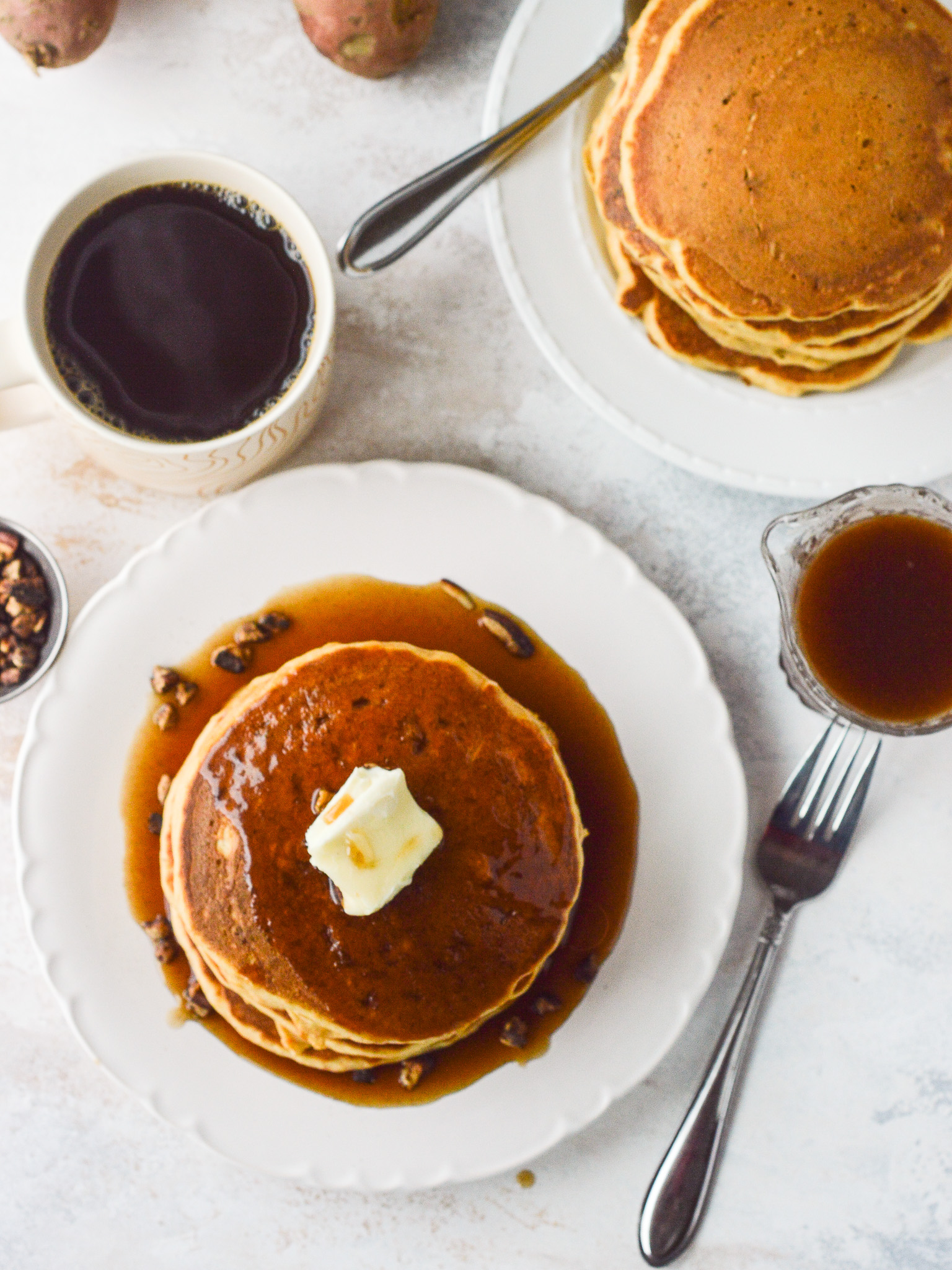 Overhead table-scape of a pancake breakfast with coffee and a carafe of cinnamon syrup