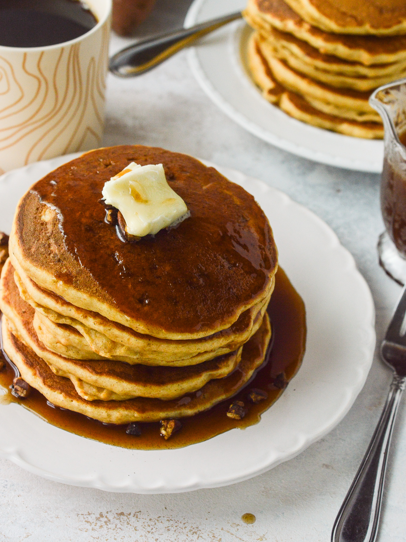Table set for two with coffee, two stacks of pancakes, and a carafe of syrup.