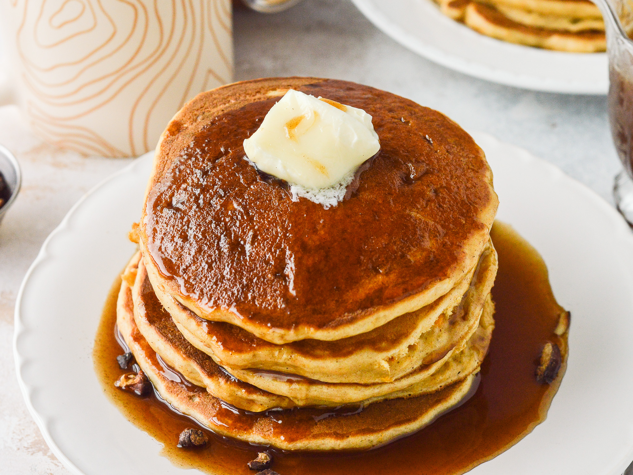 Sweet Potato Pancakes stacked on a plate with Cinnamon Syrup