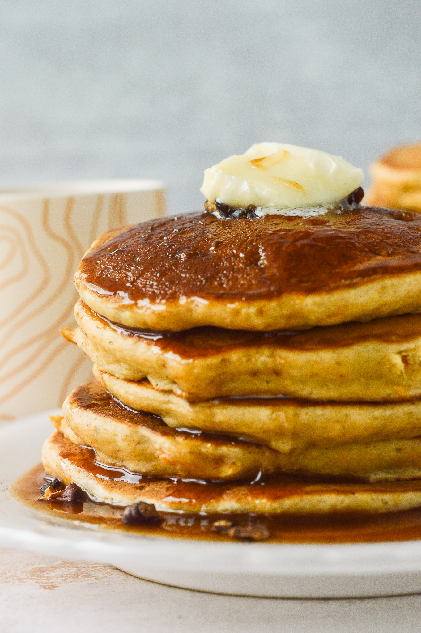 A stack of golden sweet potato pancakes topped with cinnamon syrup, a pat of butter, and toasted walnuts.