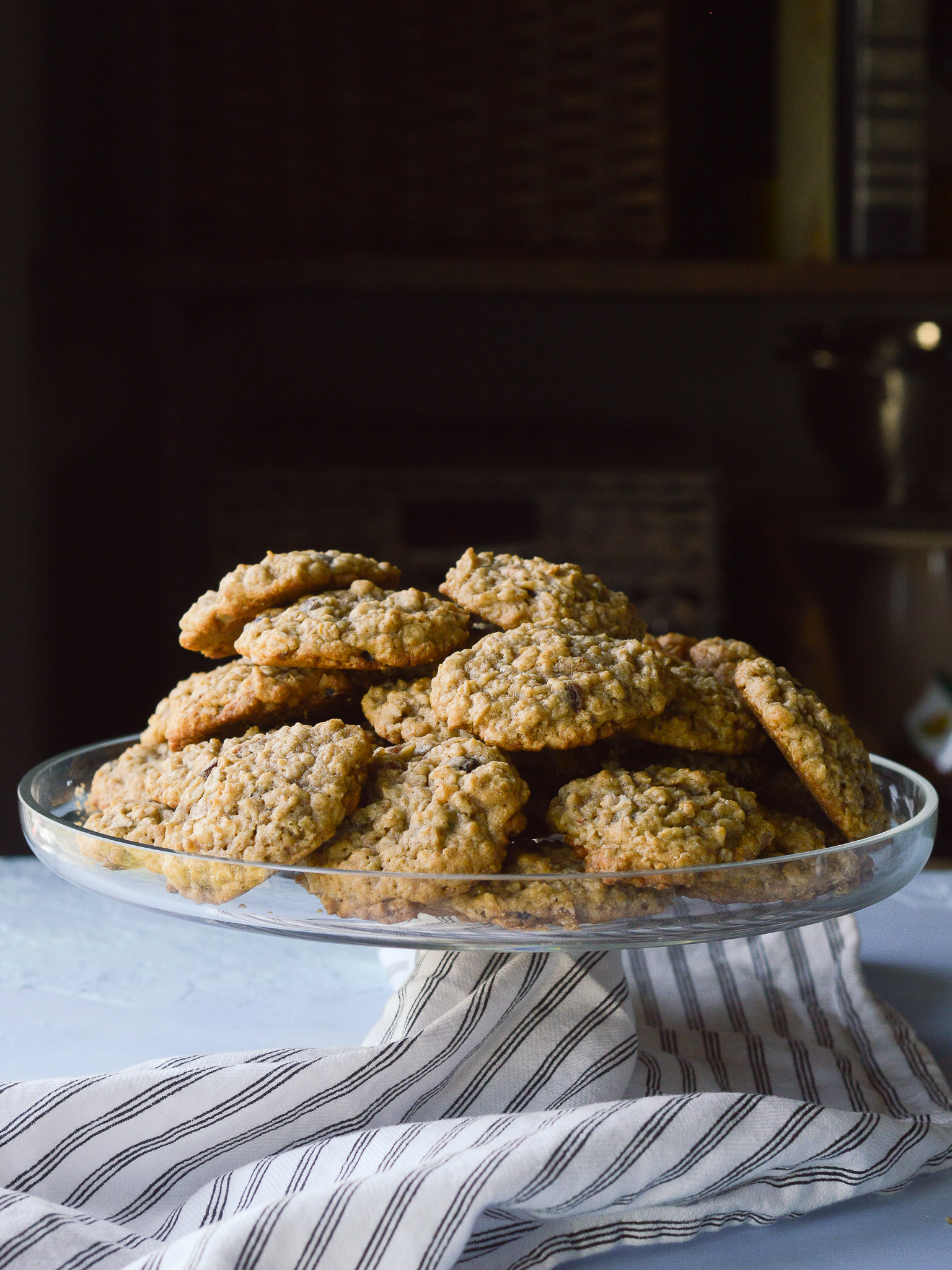 A cake stand piled high with classic oatmeal raisin cookies that are chewy with a slightly crisp edge.